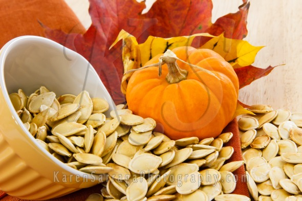 Pumpkin Seeds Spilling From A Yellow Bowl | Stock Photo